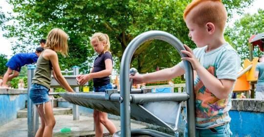 Afbeelding van schommelende kinderen in een speeltuin in een woonwijk